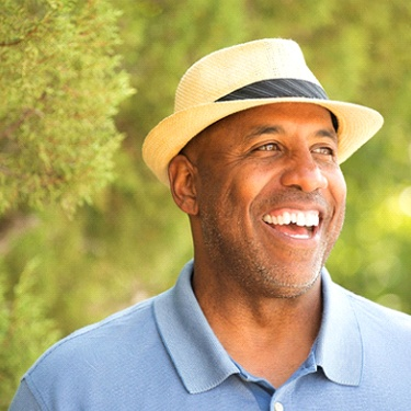 man in blue polo and fedora smiling with dental implants in Guilderland
