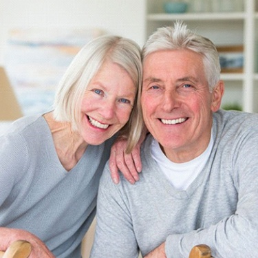 older couple smiling and wearing matching gray sweaters
