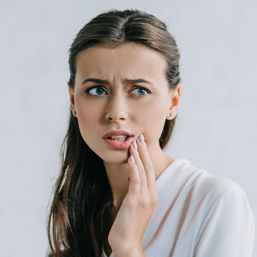Woman in need of tooth extraction holding cheek
