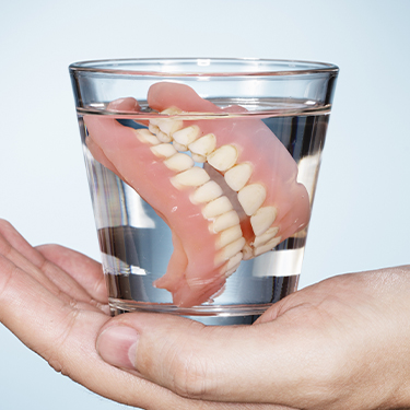 Full denture in a glass of water