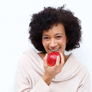 older woman biting into red apple