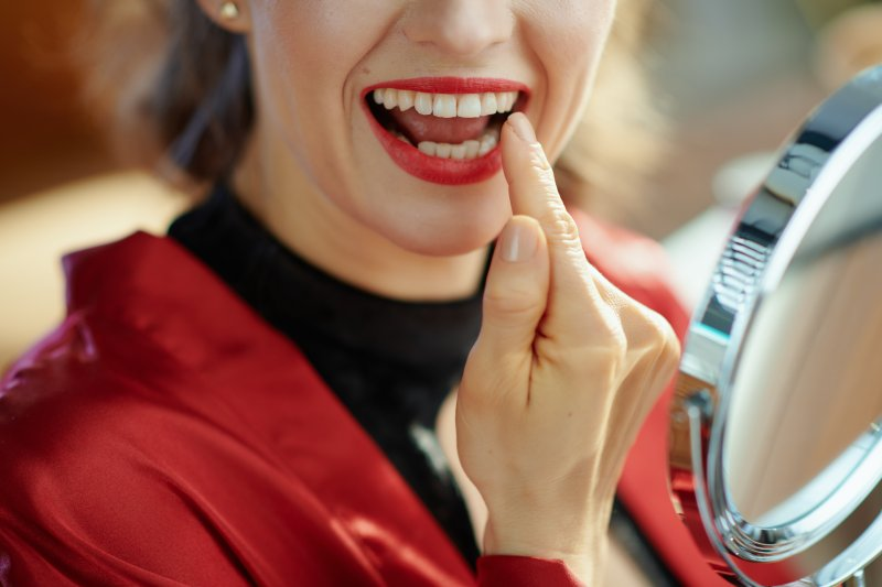 Woman pointing at smile after seeing cosmetic dentist